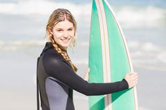 Portrait of woman in wetsuit holding a surfboard on the beach - stock photo