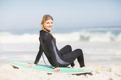 Portrait of woman in wetsuit sitting with surfboard on the beach Stock Photos