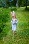 Smiling little girl with long blond hair wearing rabbit or bunny ears - stock photo