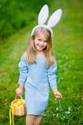Smiling little girl with long blond hair wearing white rabbit bunny ears Stock Photos