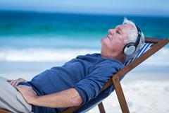 Mature man resting on a deck chair listening to music Stock Photos