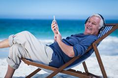 Mature man resting on a deck chair listening to music with smartphone Stock Photos