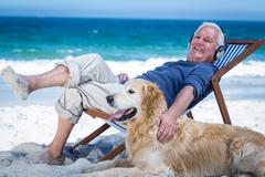 Mature man resting on a deck chair listening to music petting his dog Stock Photos