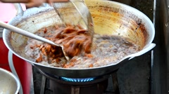Fried pork in the boiling pan in the outdoor market of Thailand. Cheap but tasty - stock footage