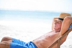 Mature man relaxing on a deck chair Stock Photos