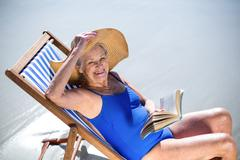 Pretty mature woman reading a book lying on deck chair Stock Photos