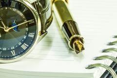 Gold fountain pen on blank notepad and watch Stock Photos