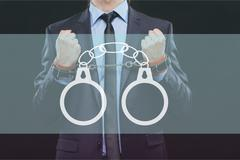 Stock Photo of man in a business suit with chained hands. handcuffs for sex games. concept of