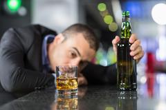 Drunk businessman slumped on bar - stock photo