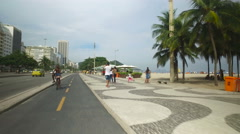 Ridding a bicycle on Copacabana Beach walkway Stock Footage