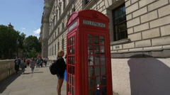 Red telephone booth on Whitehall in London - stock footage