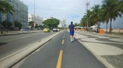 Ridding a bicycle on Copacabana Beach walkway Stock Footage