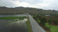 Aerial view of street by a dam with mountain background Stock Footage