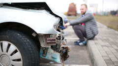 Man looking at broken car after accident - stock footage