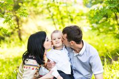 Happy mother and father kissing his little son in park Stock Photos