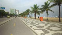 Riding a bicycle on Ipanema Beach walkway Stock Footage