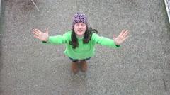 Girl turning enjoying first snow fall, aerial 4K shot Stock Footage