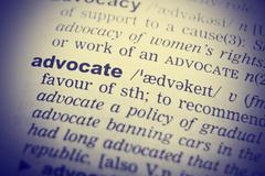 Dictionary definition of advocate. Close up view with paper textures Stock Photos