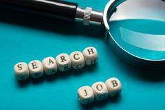 Job Search Concept. Magnifying glass and wooden block - stock photo