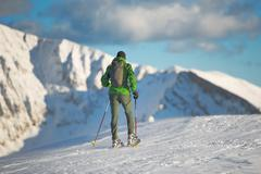 Mountaineer in winter landscape with snowshoes. - stock photo
