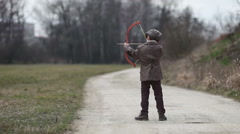 Adorable little preschool boy, shoot with bow and arrow at target in open air - stock footage