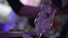 SLO MO CLOSE-UP Bartender pouring ice cubes into cocktail glass - stock footage