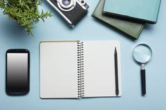 Tourism, travel concept. Office desk table with notepad, camera and supplies - stock photo