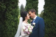 Happy wedding couple walking in a botanical park - stock photo