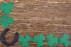 Fabric green clover leaves with horseshoe on wooden background. Stock Photos
