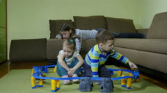 Brother and sisters playing in the room with train toy, dolly shot. Stock Footage