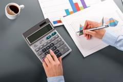 Close-up of businesswoman using calculator. Stock Photos