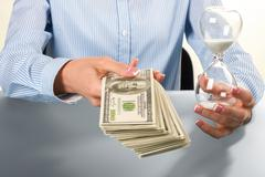 Lady holds hourglass and money. Stock Photos