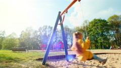 Preschooler girl  riding on a swing in the park. Sunlight - stock footage