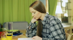 Young girl in plaid shirt reading book in the restaurant Stock Footage