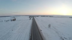 Winter road. Aerial footage. White fields covered with snow. Sunset. Stock Footage