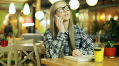Girl in glasses and plaid shirt talking on cellphone while sitting in the cafe Stock Footage