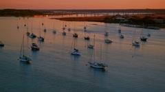 Sailboats anchored at a river by a city bay at warm sunset Stock Footage