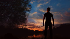 The man stand near the lake on the background of sunrise Stock Footage