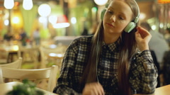 Young girl in plaid shirt listening music in the cafe Stock Footage