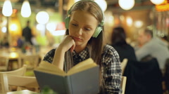 Happy girl listening music and reading book in the cafe Stock Footage