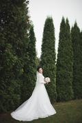 Beautiful brunette bride in elegant white dress holding bouquet posing neat - stock photo