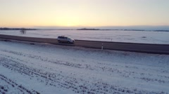 Winter road with car. Aerial footage. White fields covered with snow. Sunset. Stock Footage
