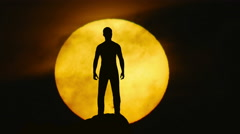 The man stand on a cliff on the background of sun. Real time capture Stock Footage