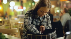 Young girl in plaid shirt looking for something in the bag Stock Footage