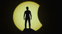 The man stand on a cliff on the background of solar eclipse - stock footage