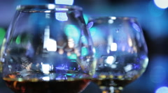 Cognac glasses at a party. Celebration at night. Glasses lit neon light. - stock footage