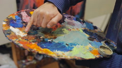 Artist brush mix color oil painting on palette is holding in his hand closeup Stock Footage