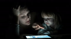 Mother and daughter enjoy the tablet at night - stock footage