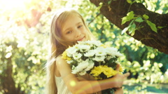 Portrait child girl hugging bouquet of flowers and smiling at camera. Sunlight Stock Footage