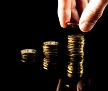 hand deliver a stack of coins graph profit growth on black background - stock photo